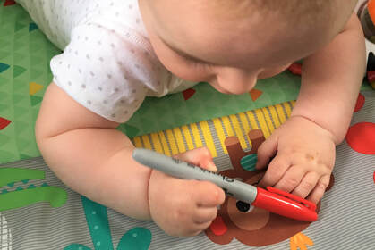 Baby holding a red pen